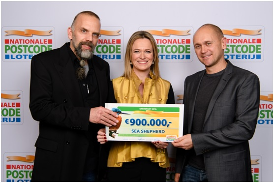 Geert Vons and Alex Cornelissen receive a check from Imme Rog, Managing Director Dutch Postcode Lottery. Photo: Roy Beusker